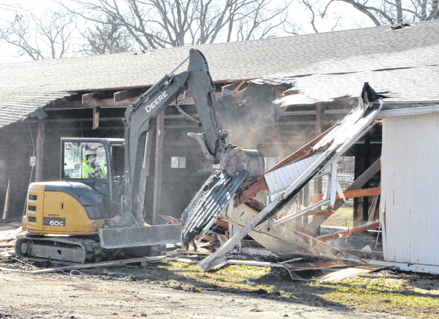 An excavator removes a piece of the Junior Fair Building on Saturday morning. The structure, which was built in the 1960s at the Delaware County Fairgrounds, is being razed to make way for the new Agricultural Center.