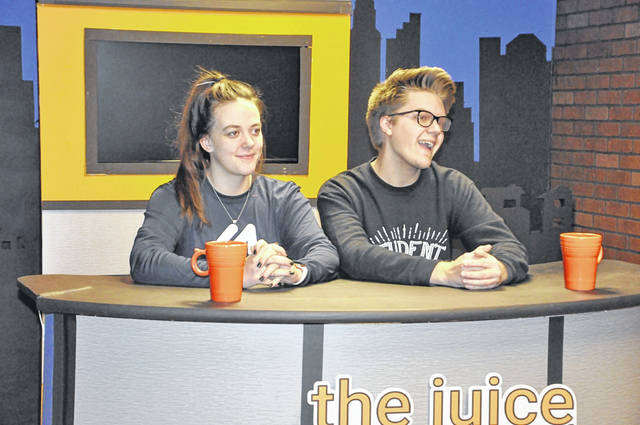 "OOHS seniors Brooke Little and Jacob Fulton sit at the desk of ""The Juice,"" the school's student news production."