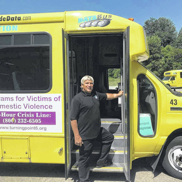 "DATA Executive Director Denny Schooley poses in front of a DATA bus. Ten buses have been equipped with books for riders to take as part of DATA's ""Books on the Bus"" program."