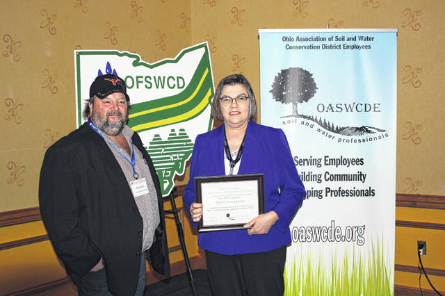 Sue Cunningham, right, of the Delaware Soil & Water Conservation District (SWCD), is recognized by Bob Short, president of the Ohio Federation of Soil and Water Conservation Districts, as the 2019 Outstanding District Board Member for her many years of excellent service on the Delaware SWCD Board of Supervisors.