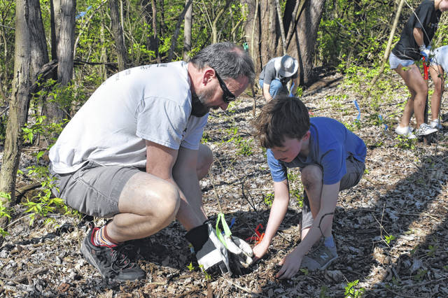 Pennsylvania residents Erik and Leif Caldwell plant a seedling in the forest at Mingo Park Monday. Erik said they were in town visiting his father, Robert Caldwell, and decided to attend the event. Erik said he grew up in Delaware and was happy to lend a hand cleaning up a place where he played as a kid.