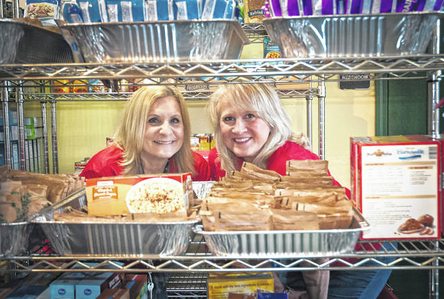 Tonya Freeman, left, and Amber Hudson, right, peak out between the shelves of the M.A.S.H. Pantry and Resource.