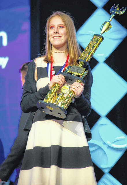 Delaware Area Career Center senior Hannah Peterson accepts her second-place trophy in the graphic design promotion category of BPA's state competition. Peterson said she had to design a logo and poster for the National Leadership Conference and do a presentation to a panel of judges.