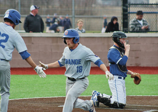 Olentangy Orange's Sam Till (18) celebrates with Matthew Wolf after scoring a run during Friday's OCC showdown against host Olentangy Liberty.