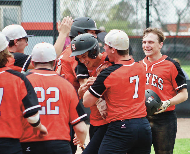 Hayes' Drew Williams, center, is mobbed by his teammates after hitting a two-run homer in the second inning of Wednesday's OCC showdown against visiting Thomas Worthington.