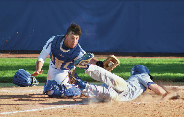 Olentangy Orange's Robbie Dayhuff slides into home as Olentangy catcher Max Caron reaches out for the tag during Monday's OCC showdown in Lewis Center.