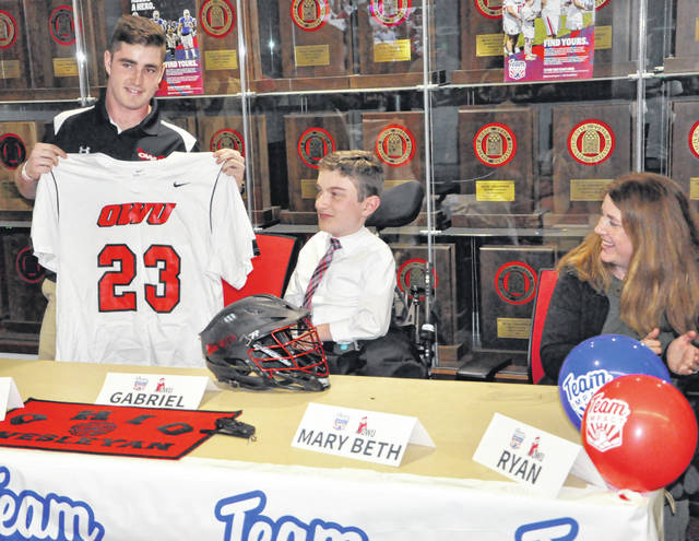 Senior Max Tennant, captain of the Ohio Wesleyan University men's lacrosse team, presents a jersey to Gabriel Eberhard, while Gabriel's mother, Mary Beth, looks on during a ceremony held Tuesday at OWU.