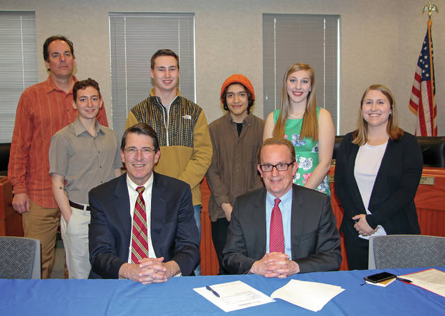 Ohio Wesleyan University and the City of Delaware celebrate a new memorandum of understanding signed on Thursday by OWU President Rock Jones (seated left) and City Manager Tom Homan (seated right) that creates a permanent student internship in the city's Department of Public Utilities. On hand for the signing are professor John Krygier (standing left), OWU environmental studies students, and Caroline Cicerchi, the city's watershed and sustainability coordinator (standing right).