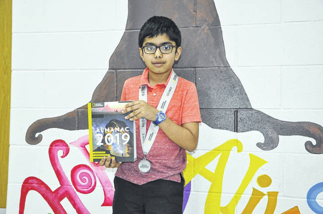 Satvik Pochiraju shows off his medal and the National Geographic Almanac he won at the National Geographic GeoBee Ohio State Competition in March. Pochiraju will head to Washington, D.C. next month to compete in the national championship.