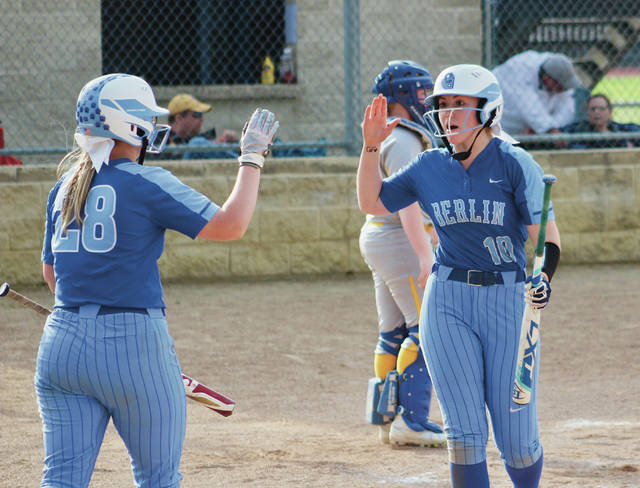 Olentangy Berlin's Kirsten Kracht (10) is congratulated by Allie Burkhart after scoring a run during Tuesday's Division II district tournament game against host Buckeye Valley.