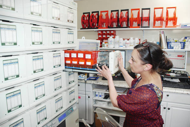 Jessica Smith, a pharmacy technician, works on custom packaging of medicines at Resident Care Pharmacy, located in The Medicine Shoppe building at 821 Scioto St., Urbana.