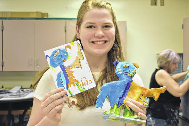 Hayes sophomore Maria Schul holds up the monster she created in ceramics class based on a drawing done by a Woodward Elementary student.