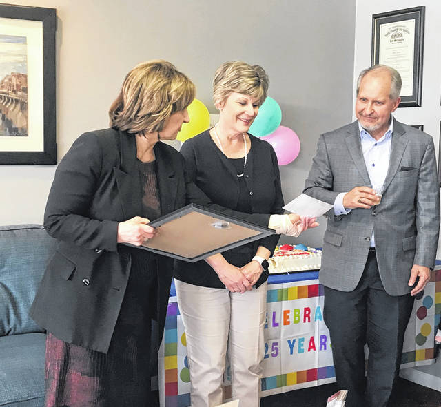 Delaware Area Chamber of Commerce President Holly Quaine shows Don & Sherri Hughes their 25th anniversary proclamation from the chamber and a vintage 1997 ribbon-cutting ceremony photograph.
