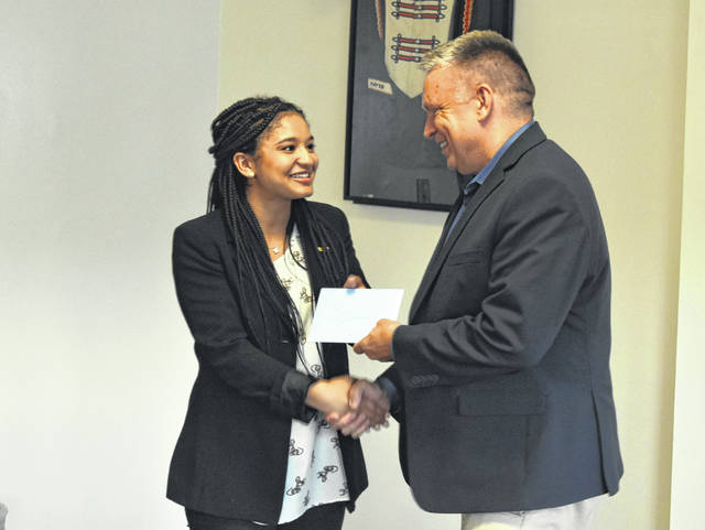 Caroline Binkley, the outgoing student member of the Delaware City Schools Board of Education, shakes hands with Superintendent Paul Craft after being presented a gift during Monday's meeting.