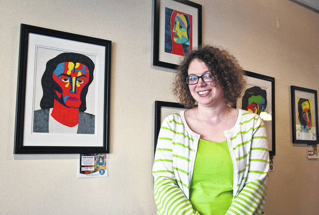 Local abstract artist Katie Rhoades stands with some of her artwork currently on display at J. Gumbo's in downtown Delaware.