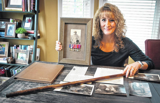 Next week, Beth Rieman, of Delaware, will travel to the beaches of Normandy, France, to donate the cane used by Brig. Gen. Teddy Roosevelt Jr. to direct troops at the D-Day invasion to the Musée du Débarquement (D-Day Museum) in France. Rieman, holding the cane and a photo of her great-granduncle James S. Rodwell, was recently led to the cane as she researched her uncle's involvement in the historical event through some carefully preserved military papers and newspaper clippings.