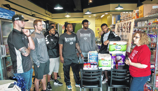 "Players from the Arena Football League's Columbus Destroyers took time from their practice schedule Tuesday to pay a visit to the Delaware M.A.S.H. Pantry. After the team carried in several donations, M.A.S.H. Pantry Coordinator Tonya Freeman, far right, told the players a little about the pantry and the things it does for veterans. The number one thing she told them is ""everyone that comes through the door gets a hug."""