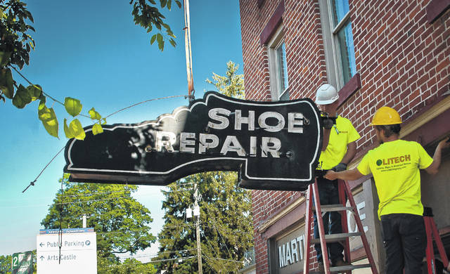 After unbolting the 56-year-old antique Shoe Repair sign, (L-R) Joe Marek, owner of Litech Lighting Management Services, and his son Jake Marek cautiously guide the sign to the sidewalk in front of the doorway that it hung over for many years.