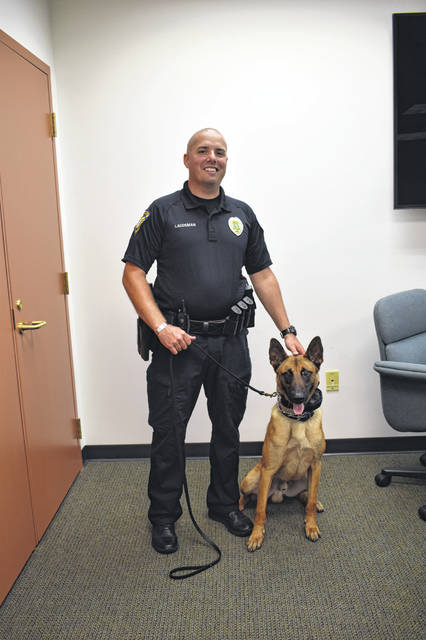 "City of Delaware Police Officer John Laudeman and his partner, Tyson, pose together Thursday in the police station. Laudeman and Tyson have been working together for the last seven weeks, and Laudeman said working with Tyson is like ""magic."""
