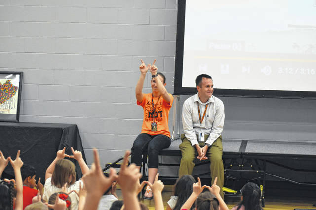 """Students and staff form their hands into a """"W"""" for Woodward as a gesture of thanks for Malany Tuesday. Malany told the students that he loved them and was proud of them."""