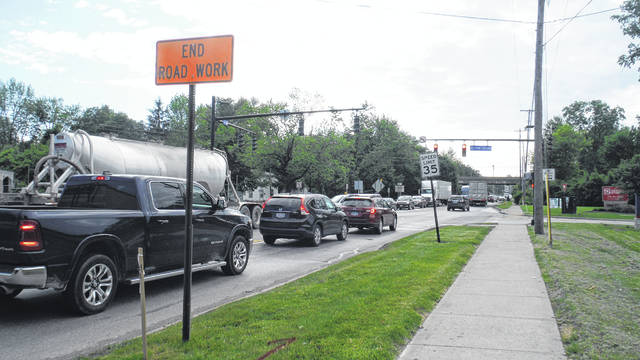 "Traffic travels past an ""End Road Work"" sign going east on William Street by The Point intersection in Delaware Friday morning."
