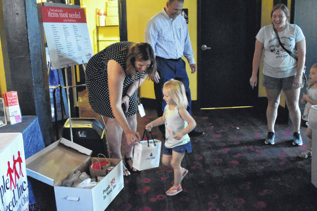 """Delaware City Schools Assistant Superintendent Heidi Kegley helps Isabella Wood, 2, put donations into a box for People In Need Tuesday at the Strand Theatre. Wood attended the screening of """"The Ant Bully"""" with her friend, Ella Hoffman, 3, and her mother, Jessica Ladd."""