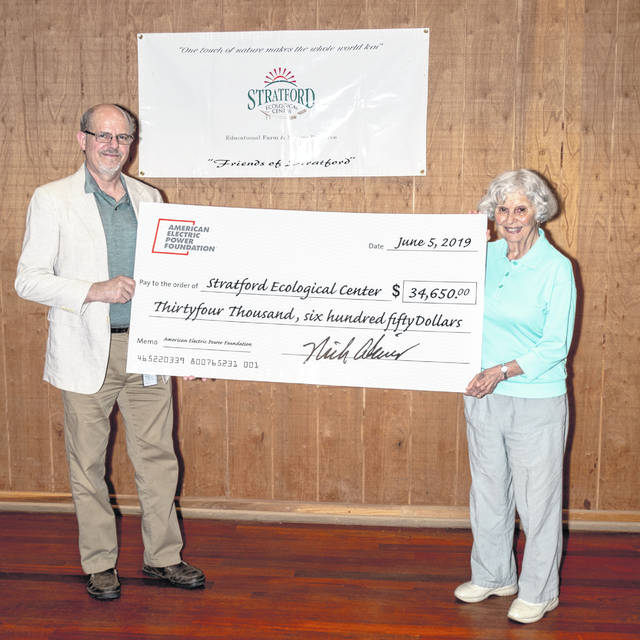 Pictured is Louise Warner, originator of the Stratford Ecological Center, accepting a check from Barry L. Schumann, a representative from the American Electric Power Foundation.