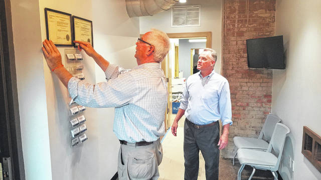 City of Delaware Chief Building Official Jerry Warner hangs state certifications in the new offices of the Planning and Community Development Department as department director Dave Efland looks on. It marks the first expansion of City Hall work space in more than 25 years, the last coming when City Hall was renovated in 1992.
