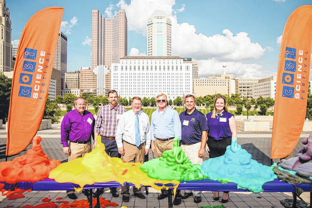 Delaware Vice Mayor Kent Shafer, fourth from the left, poses for a photo with the aftermath of a science experiment at COSI in Columbus. Shafer was on hand Tuesday, along with the mayors from five other cities, for the announcement of COSI's Science Festival expanding to their cities.