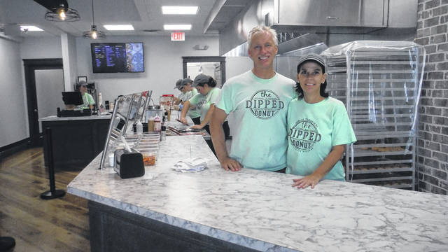 Carl and Jeni Reida stand behind the counter at The Dipped Donut.
