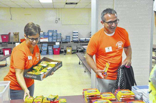 Schultz Elementary School Principal Travis Woodworth and volunteer Stephanie Manor gather school supplies for an elementary school student during Delaware City Schools' Supplies for Scholars event in July 2017. This year's event will allow students to get free school supplies, check-ups and haircuts.