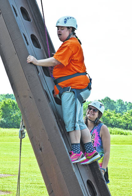 "Kelly Shoemaker received cheers of encouragement as she made an attempt to climb to the top of Recreation Unlimited's climbing tower. Next to her is Megan Clouse, who encouraged Shoemaker to climb to the platform by saying, ""I believe in you, Kelly."""