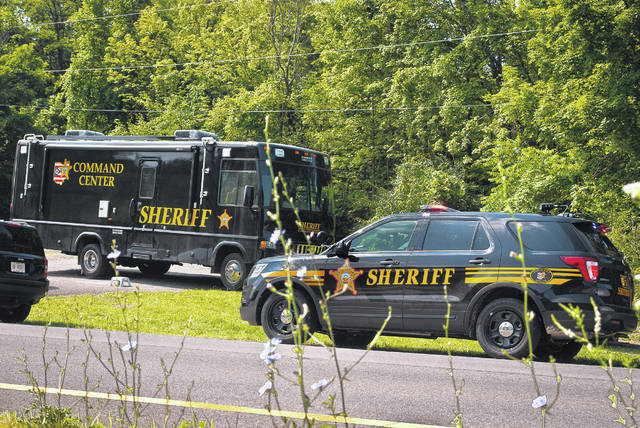 Vehicles from the Delaware County Sheriff's Office block the Alum Creek State Park pull-off area on the east side of the bridge near the 6400 block of U.S. Route 36/state Route 37 Friday. A body was discovered in a shallow grave near the site Thursday.