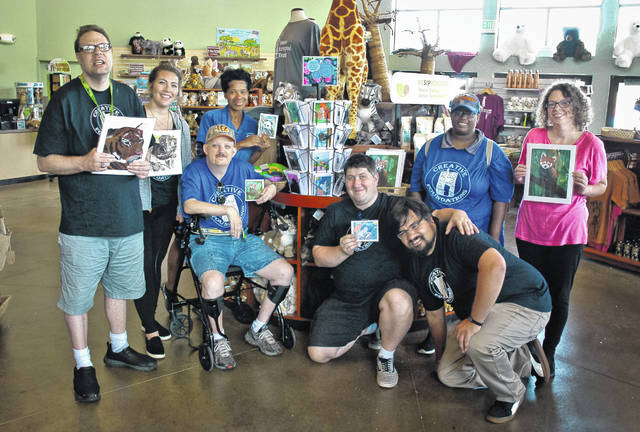 The Columbus Zoo and Aquarium and Creative Foundations have formed a new partnership in which the zoo is now selling artwork of animals created by local artists with developmental disabilities. Many of the artists met Thursday at the gift shop to talk about what they can do to support the zoo with their work. Pictured, left to right, holding some of the work sold at the zoo gift shop are (back row): Bryan Burks, Kelly Jacoby, gift shop spokesperson Deidre Harris, Kyra Warren and Katie Rhoads; and (front row): Dave Bamford, Paul Day and Nikko Makua.