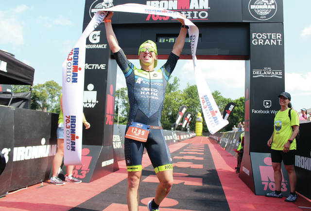 Eric Engel celebrates after crossing the finish line at the Ironman 70.3 Ohio Sunday in Delaware. Engel finished with the top overall time of 4:01.53.