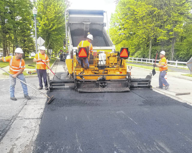 Crews pave a section of roadway in this file photo provided by the City of Delaware.