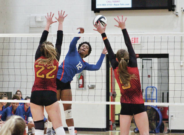 Olentangy Orange's Tazmin Appiah (12) hammers a shot past Big Walnut's Caroline Speelman (22) and Kassie Bowmar during the first set of Tuesday's non-league showdown in Sunbury.