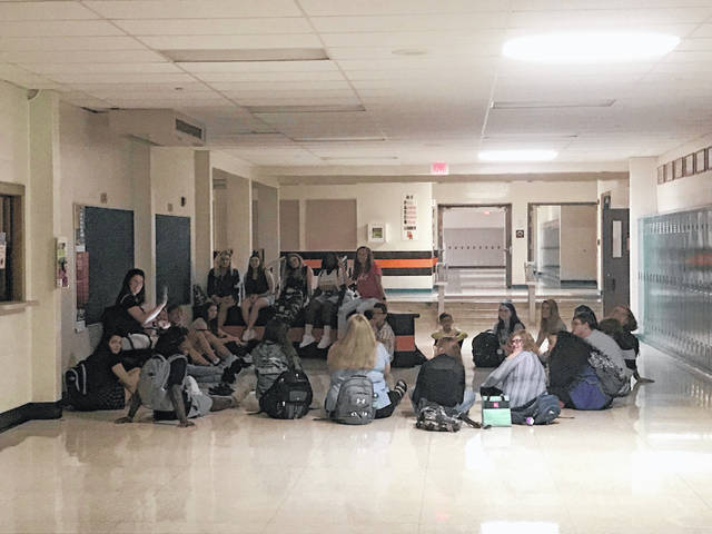 Students in a yoga class at Hayes High School have class in the hallway Wednesday after a power outage rendered the auxiliary gym too dark to use. Power went out just after 8:15 a.m. and was restored around 9:30 a.m.