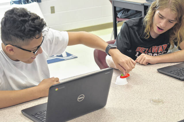 Ethan Long, left, and Jeremiah Rutherford, right, attempt to rescue Sam the gummy worm using paper clips to stretch a gummy Lifesaver around him.