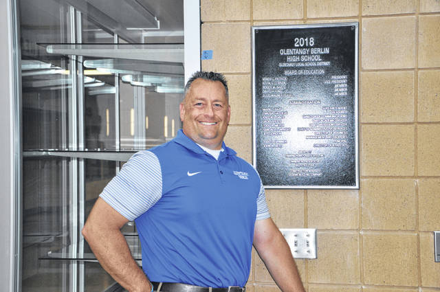 Prior to the opening of Olentangy Berlin High School last August, Principal Todd Spinner stands in front of the district staff and school administration plaque that adorns the entrance to each OLSD high school.