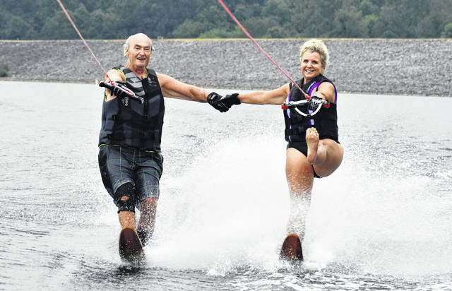 Ray McCurry's 50-year passion for water-skiing evolved into a family affair that now includes his four children, seven grandchildren, and his great-grandchildren. Pictured is McCurry, left, water-skiing hand-in-hand with his daughter, Kathleen Bensi, on Alum Creek Wednesday morning. Bensi, 55, shows off one of her many tricks by skiing on one leg while extending the other leg straight out in front of her.