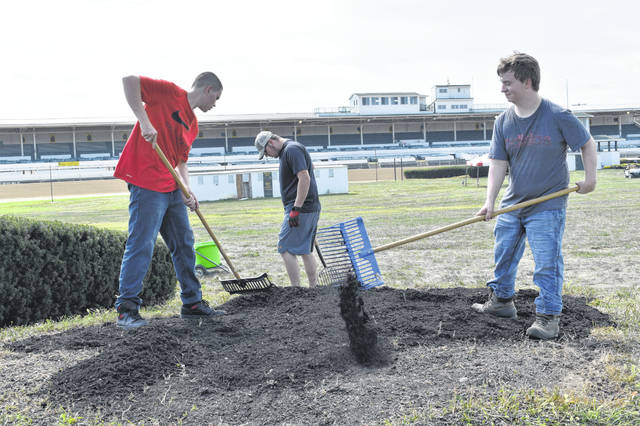 "Delaware Area Career Center Landscaping Architecture students mulch the ""Little Brown Jug"" hedge located in the infield of the racetrack at the Delaware County Fairgrounds Wednesday. From left to right: Matthew Love, James Cannon and Brandon Hudson. Cannon said he was excited for everyone at the fair to see the work they had done."