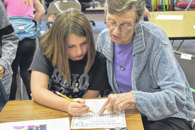 Linda Rohr and her granddaughter, third grader Kiley Davis, do a word search puzzle together Friday morning in Dianna Wise's class at Schultz Elementary School. The puzzle was one of several activities third graders did with their grandparents.