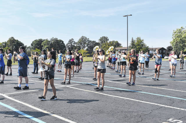 The band practices marching in unison and formation Tuesday. On Saturday, the band will perform their show at a competition where judges will grade them on music, drill, technique and other criteria.