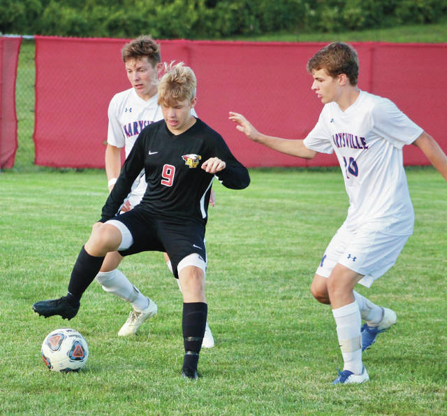 Big Walnut's Cody Lumby, center, controls the ball as Marysville's Luke Holle, left, and Joey Duke defend during the first half of Tuesday's non-league showdown in Sunbury.