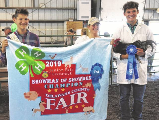 Siblings from the Wecker family celebrate following the Showman of Showmen contest held Wednesday at the Delaware County Fair. Pictured, left to right, are Junior Fair royalty Zack, former royalty and event champion Madelyn, and current champ Cole with his Jersey giant rooster.