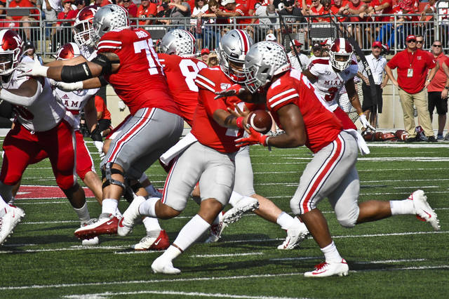 Ohio State quarterback Justin Fields hands the ball off to running back J.K. Dobbins in the first half of their game against Miami (OH).