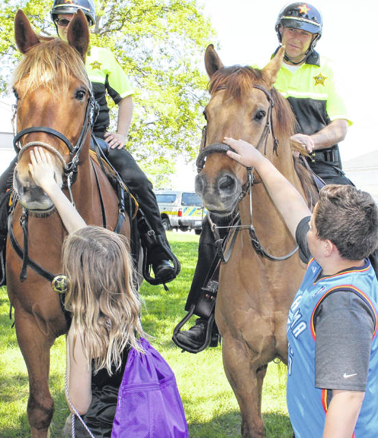 Fifth graders touch two horses ridden by mounted deputies from the Delaware County Sheriff's Office at Safety Day earlier this year. Steve Jones, top right, and his horse, Chester, will be on patrol throughout the fair.