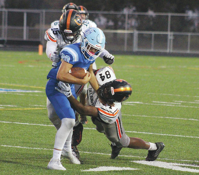 Delaware Hayes' Nabil Abdus-salaam (84) and Jacob Hunsaker (15) combine to tackle Olentangy Berlin's Nick Tiberio during the first half of Friday's league showdown in Delaware.