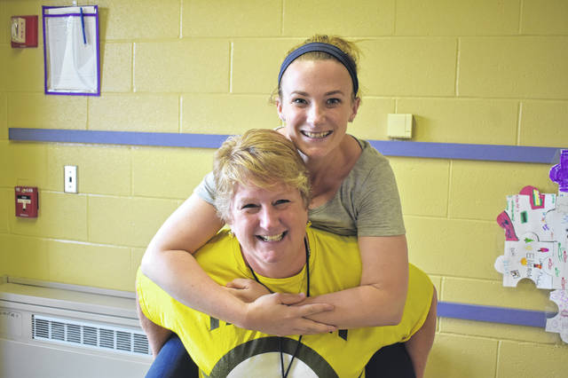 Schultz Elementary School second grade teachers Emily Thornlow, top, and Jennifer Larrison, bottom, pose together Friday afternoon just before it was announced the school raised $1,719 for charity.